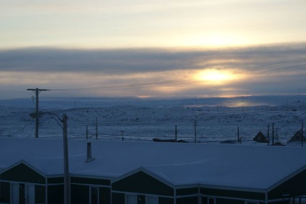 The sun setting behind clouds around 2 pm today. Perspective: where our bishop is visiting in Pond Inlet, they're down to 45 minutes of light.